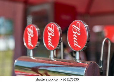 KIEV, UKRAINE - JUNE 28, 2017: Three shining beer faucets with red plates Bud beer closeup. Budweiser is an American style pale lager produced by the multinational corporation Anheuser-Busch InBev.