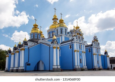 KIEV, UKRAINE - June 29, 2016: Michael's Golden-domed monastery is an architectural building of an orthodox blue church with white columns and golden domes with a cross.