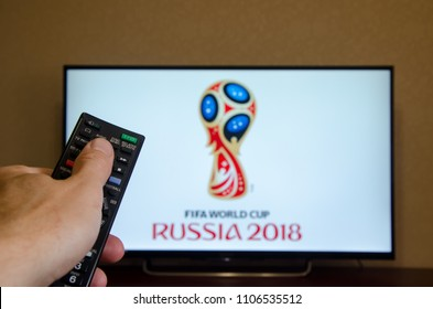 Kiev, Ukraine- June 5, 2018: Man watching 2018 FIFA World Cup Russia™ on TV and using remote controller.