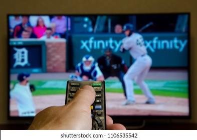 Kiev, Ukraine- June 5, 2018: Man watching Major League Baseball on TV and using remote controller.