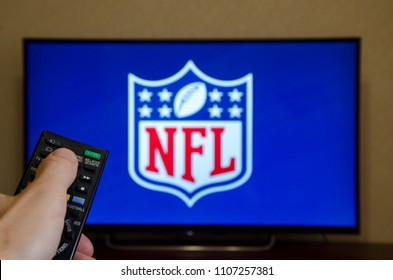 Kiev, Ukraine- June 5, 2018: Man watching National Football League (NFL) on TV and using remote controller.