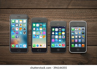 Kiev, Ukraine - March 05, 2016: Front view of a space grey color iPhones 6, 5s, 4 and 3gs generation showing the home screens on wooden background.