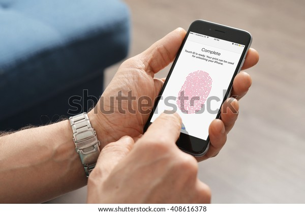 Kiev, Ukraine - March 06, 2016: Man using touch ID scanner of fingerprints on  iPhones 6, developed by Apple corporation. Allows users to unblock the smartphone and to make purchases.