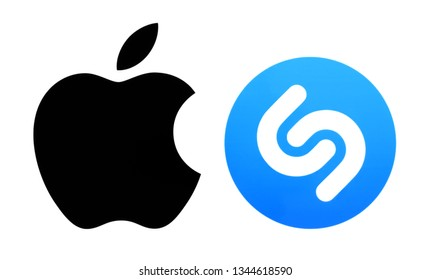 Kiev, Ukraine - March 12, 2019: Popular brand logos printed on paper: Apple ios and Shazam. Apple confirms it has acquired Shazam