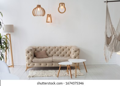 KIEV, UKRAINE - March 12, 2020: brown sofa and hammock on a background of a white wall in a natural interior. Scandinavian interior