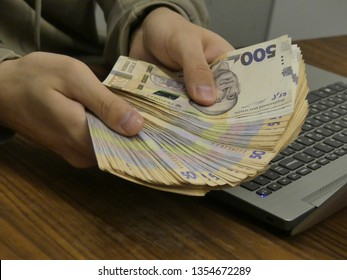 Kiev, Ukraine - March 2019: Bundle of Ukrainian money. Ukrainian hryvnia money. A stack of money in the hands near the computer. Money in hand against the background of a computer keyboard.