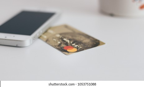 Kiev, Ukraine - March 23, 2018: Mastercard credit card and mobile phone on white background