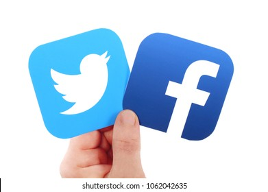 Kiev, Ukraine -  MARCH  24, 2018: Hand holds Facebook and  Twitter icons printed on paper on blue paper background. Facebook is a well-known social networking service
