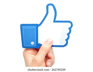 KIEV, UKRAINE - MARCH 7, 2015: Hand holds facebook thumbs up sign printed on paper on white background. Facebook is a well-known social networking service.
