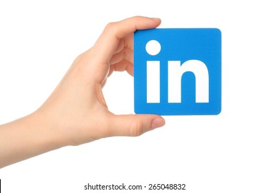 KIEV, UKRAINE - MARCH 7, 2015: Hand holds Linkedin logo sign printed on paper on white background. Linkedin is a business social networking service.