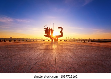 Kiev, Ukraine - May 05, 2018: Monument to the founders of Kyiv (Kiev) at sunrise, wide-angle view with blue sky and yellow sun. Statue of Kyi, Shchek, Horyv and Lybid. Kyiv the capital of Ukraine
