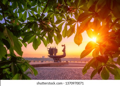 Kiev, Ukraine - May 05, 2018: Founders of Kiev monument at sunrise through the blossoming chestnut flowers and green leaves, beautiful city view with rising sun and fiery sky, capital of Ukraine