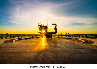Kiev, Ukraine - May 05, 2019: Monument to the founders of Kyiv (Kiev) at sunrise, wide-angle view with blue sky and yellow sun. Statue of Kyi, Shchek, Horyv and Lybid. Kyiv the capital of Ukraine