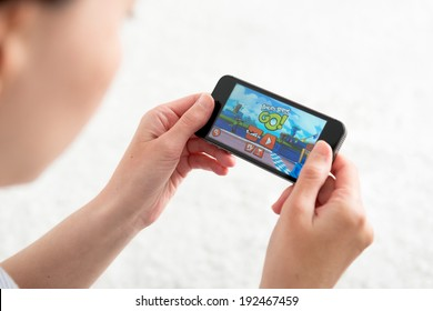KIEV, UKRAINE - MAY 10, 2014: Woman playing Angry Birds Go! a kart racing mobile game application. This is the seventh part of the Angry birds game series, and was released on November 26, 2013.