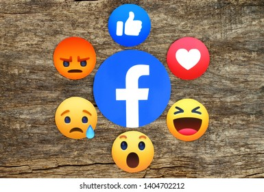 Kiev, Ukraine - May 10, 2019: New Facebook like button 6 Empathetic Emoji Reactions printed on paper and placed on wooden background. Facebook is a well-known social networking service