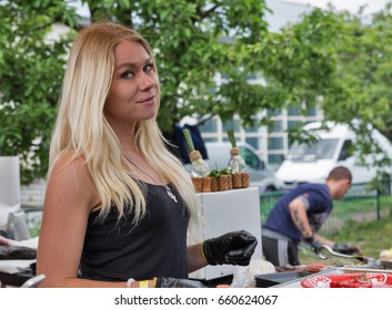 KIEV, UKRAINE - MAY 14, 2017: Unrecognized young blonde woman works in food court of Kyiv Food and Wine Festival in National Expocenter, a permanent multi-purpose exhibition complex.
