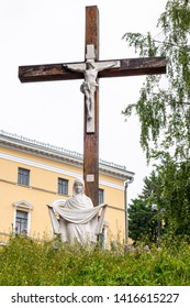KIEV, UKRAINE - MAY 15, 2014: Low angle outdoor view of a large wooden cross with Jesus crucified and Holy Mary underneath with a building in the background in Kiev Ukraine May 15, 2014.