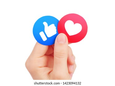 Kiev, Ukraine - May 15, 2019: Hand holds new Facebook Like and Love Empathetic Emoji Reactions, printed on paper. Facebook is a well-known social networking service