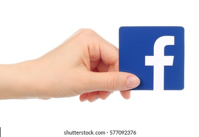 Kiev, Ukraine - May 17, 2016: Hand holds Facebook icon printed on paper. Facebook is a well-known social networking service.