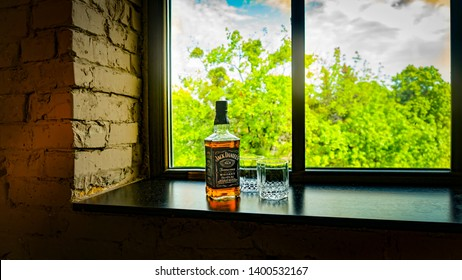 Kiev, Ukraine, May 17, 2019, a bottle of Tennessee Whiskey Jack Daniel's Old No.7  and whiskey glasses near the window with a beautiful view