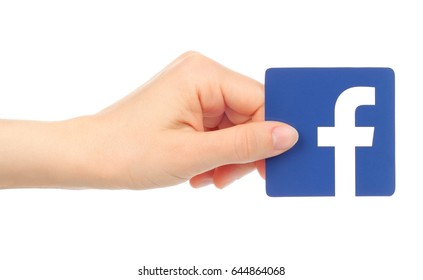 Kiev, Ukraine - May 18, 2016: Hand holds Facebook icon printed on paper. Facebook is a well-known social networking service