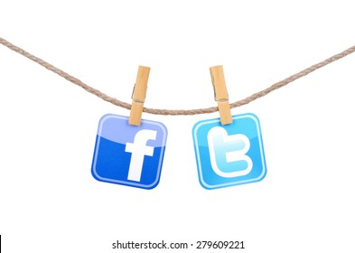 KIEV, UKRAINE - MAY 19, 2015: Popular social media Facebook, Twitter hanging on the clothesline isolated on white background.