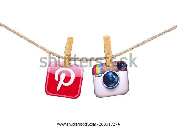 KIEV, UKRAINE - MAY 19, 2015: Popular social media  instagram, pinterest  hanging on the clothesline isolated on white background.
