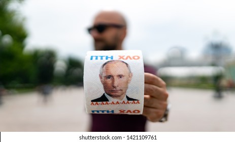 KIEV, UKRAINE - MAY 2019: Man holding Toilet paper with Russian President Vladimir Putin portrait. Illustrative editorial.