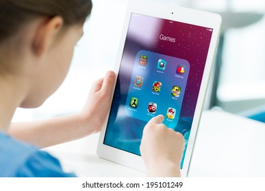 KIEV, UKRAINE - MAY 21, 2014: Little girl looking on a brand new Apple iPad Air with various game applications on a screen. Apple iPad Air developed by Apple inc. and was released on November 1, 2013.