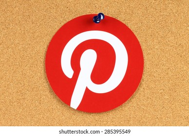 KIEV, UKRAINE - MAY 25, 2015:Pinterest logotype printed on paper and pinned on cork bulletin board. Pinterest is photo sharing website.