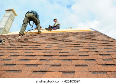 KIEV - UKRAINE, MAY - 25, 2016: Roofing Contractors Install New House Roofing with Asphalt Shingles. Roofer working on a home with safety rope. Roofing Contractor.
