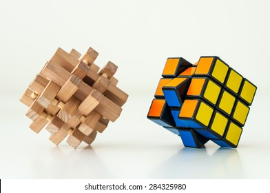 KIEV, UKRAINE - MAY 26, 2015: Wooden Brain Teaser and Rubik's cube on the white background. Rubik's Cube invented by a Hungarian architect Erno Rubik in 1974.