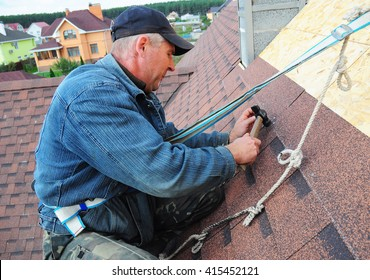 KIEV - UKRAINE, MAY - 3, 2016: Roofing Contractor. Roofing Construction and Building New House Exterior. Roofer  Install, Repair Asphalt Shingles or Bitumen Tiles on the Rooftop Outdoor.