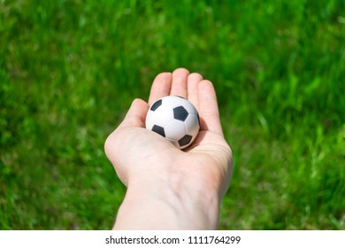 KIEV, UKRAINE - MAY 31, 2018: Football ball in female hand on background of green grass. Toy soccer ball in the palm on background of green football field