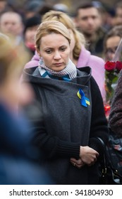 KIEV, UKRAINE - Nov 21, 2015: Laying flowers at the memorial cross in the Alley of Heroes of the celestial hundreds in place of the mass shooting of protesters on February 20