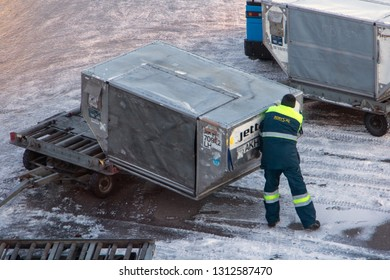 KIEV, UKRAINE, NOV 28 2018, A ground staff of the airport manipulate the freight container. The man is loading a large heavy container on a cart on winter airport.