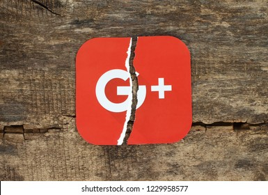 Kiev, Ukraine - November 07, 2018: Google plus icon printed on paper, torn and put on old wooden background. Google is shutting down Google+, admits low consumer adoption.