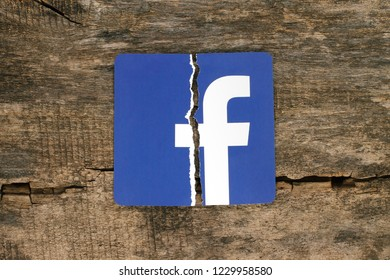Kiev, Ukraine - November 07, 2018: Facebook icon printed on paper, torn and put on old wooden background. Facebook security and privacy issues concept.