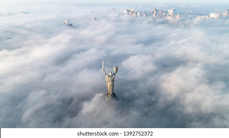 KIEV, UKRAINE - NOVEMBER 10, 2018: Thick clouds of autumn fog and the Motherland monument sticking out of them. City in the mist