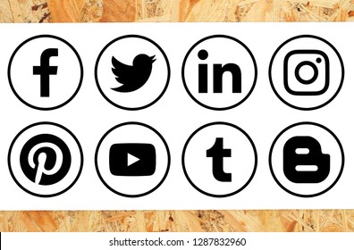 Kiev, Ukraine - November 16, 2018: Collection of popular black circle social media icons with rim printed on paper on wooden background: Facebook, Twitter, Instagram, Pinterest, Blogger and others
