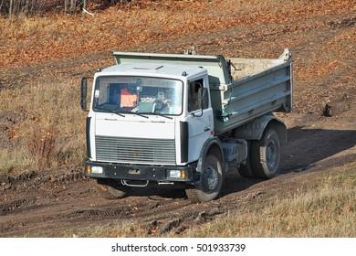 Kiev, Ukraine - November 23, 2010: Dump truck is driving along the muddy road