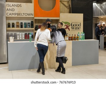 KIEV, UKRAINE - NOVEMBER 25, 2017: Unrecognized young women visit Good Wine store Single Malt Scotch Whisky booth at 3rd Ukrainian Whisky Dram Festival in Parkovy Exhibition Center.
