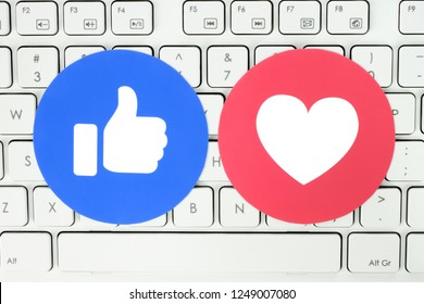 Kiev, Ukraine - November 28, 2018: Facebook Like and Love button of Empathetic Emoji Reactions printed on paper and put on white keyboard.