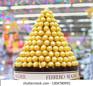 Kiev, Ukraine - November 29, 2019. Pyramid from Ferrero Rocher candies, a famous chocolate candies on shelves in the Auchan store. Ferrero Rocher is a famous brand of candies.