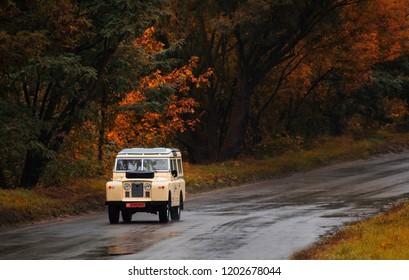 KIEV, UKRAINE - OCTOBER 01, 2018: vintage car Land Rover Defender on the autumn forest road. Retro vehicle moving on the highway in autumn landscape.  Automotive photography.