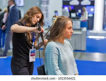 KIEV, UKRAINE - OCTOBER 07, 2017: Hairdresser makes hairstyle on Remington booth, personal care corporation, during CEE 2017, largest electronics trade show of Ukraine in ExpoPlaza Exhibition Center.