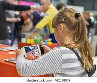 KIEV, UKRAINE - OCTOBER 07, 2017: Young girl visit Motorola, an American multinational telecommunications company booth during CEE 2017, largest electronics trade show of Ukraine in KyivExpoPlaza EC.