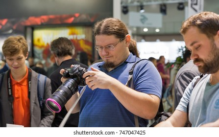 KIEV, UKRAINE - OCTOBER 07, 2017: Unrecognized visitors testing professional photographic cameras on Nikon booth during CEE 2017, the largest electronics trade show of Ukraine in KyivExpoPlaza EC.