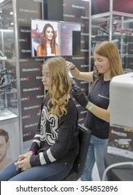 KIEV, UKRAINE - OCTOBER 11, 2015: Hairdresser makes hairstyle on Remington booth, personal care corporation, during CEE 2015, largest electronics trade show of Ukraine in ExpoPlaza Exhibition Center.