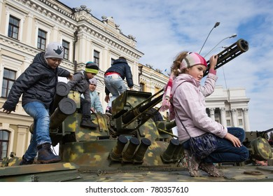 KIEV, UKRAINE - October 14, 2015: Children play on the tank at the exhibition of military equipment in central Kiev, Ukraine.